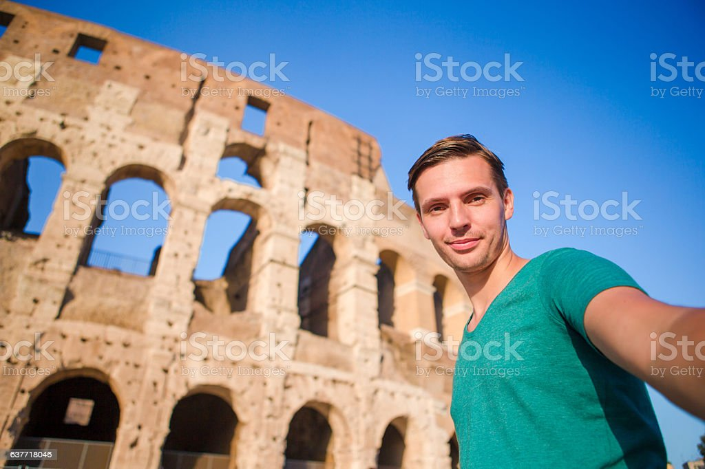 Young man taking selfie portrait in front of Colosseum in stock photo