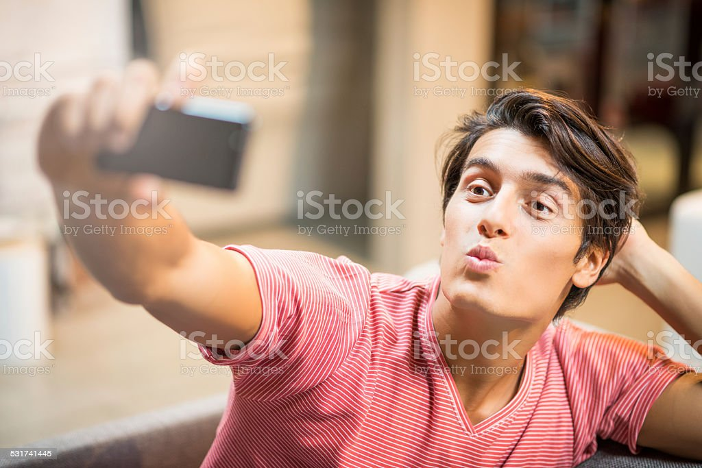 Young man taking selfie with phone stock photo