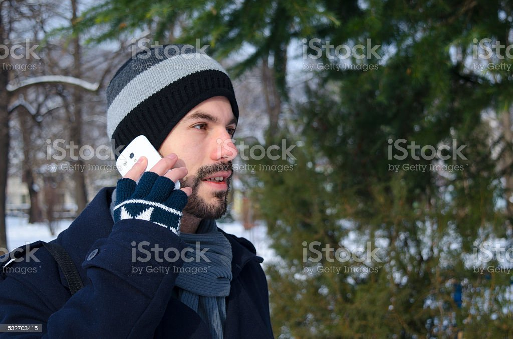 Young man talking on a smartphone in winter time royalty-free stock photo