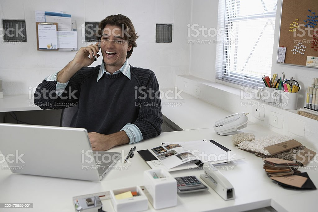 Young man talking on cell phone and using laptop at desk, laughing stock photo