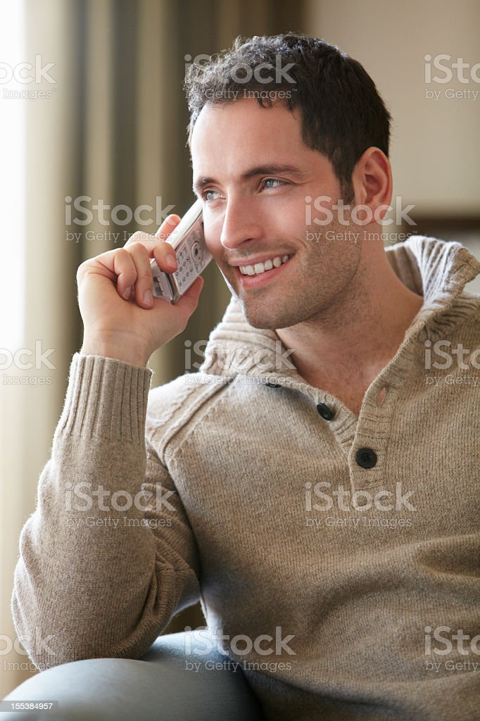Young man talking on cordless phone at home stock photo