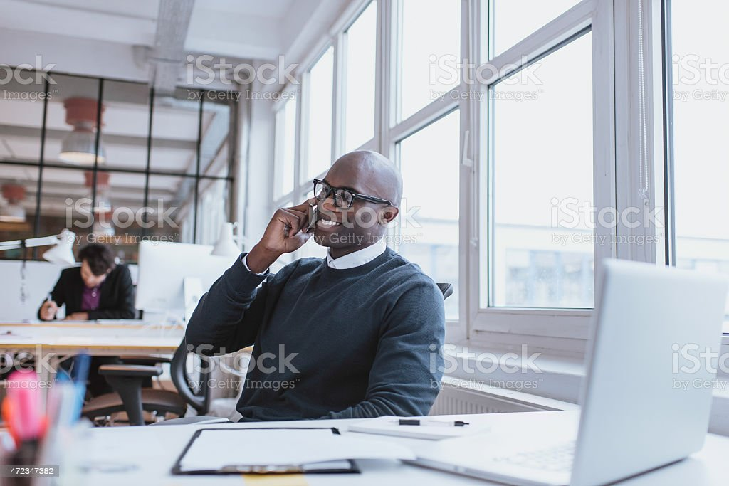 Young man talking on his mobile phone in office stock photo
