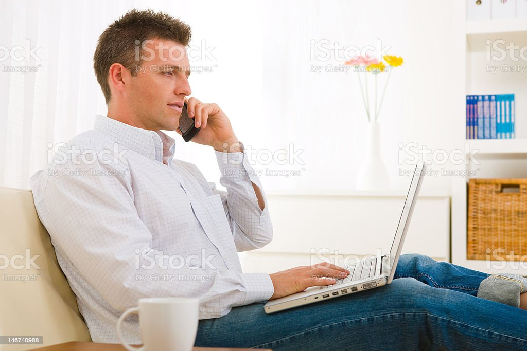 Young man talking on the phone and working on his laptop royalty-free stock photo