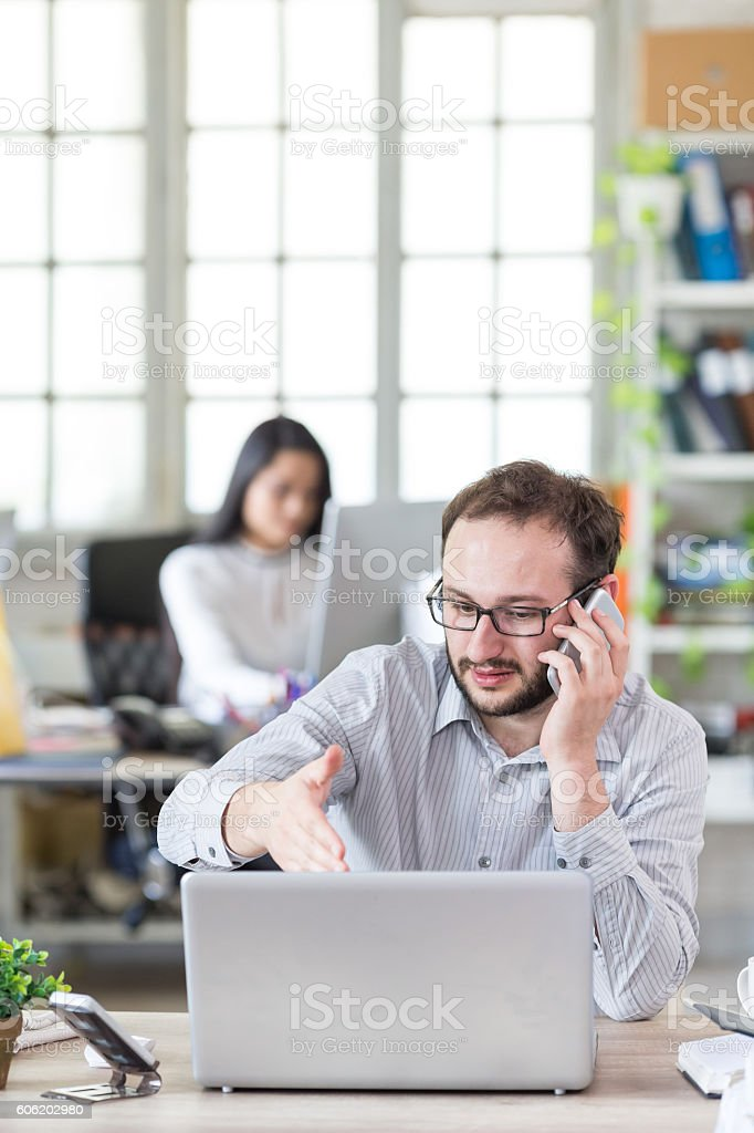 Young man talking on the phone at the office stock photo