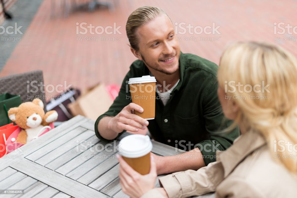 young man talking with his girlfriend while drinking disposable coffee at cafe stock photo