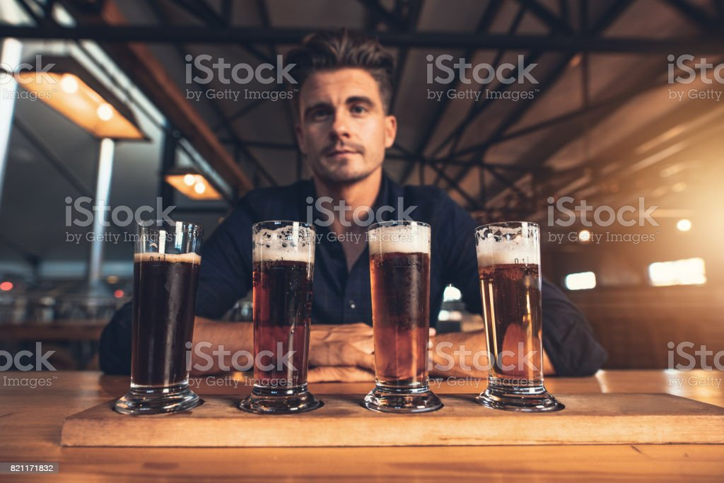 Young man tasting different varieties of craft beer on a wooden table...