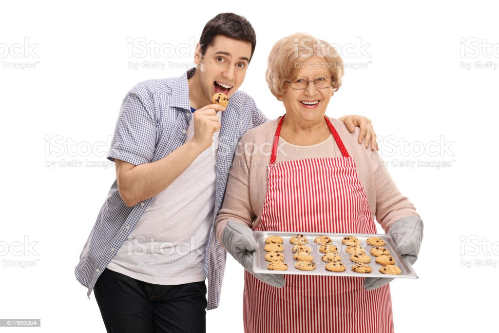 Young man tasting freshly baked cookie by his grandmother stock photo
