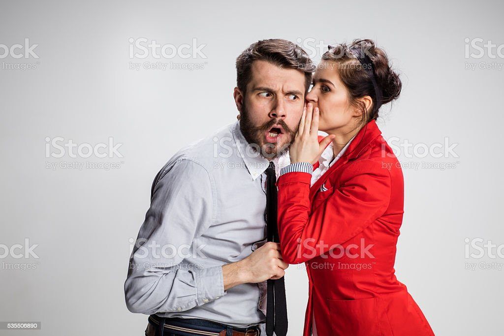 Young man telling gossips to his woman colleague at the stock photo