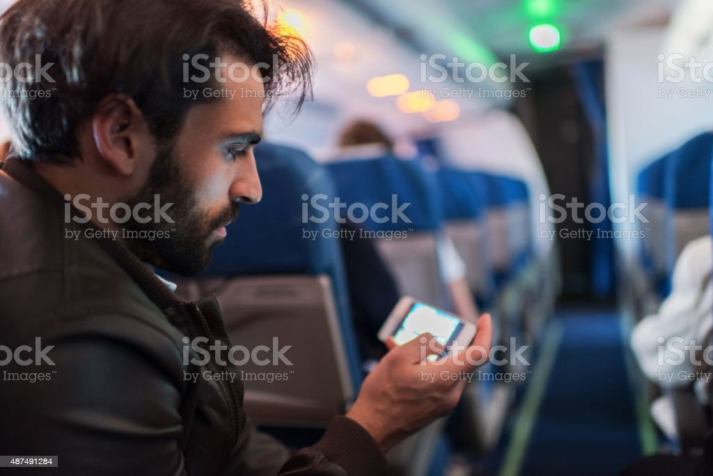 Young man text messaging on mobile phone in airplane. stock photo