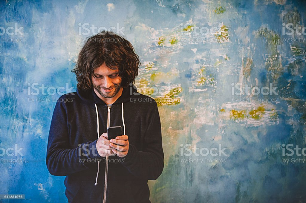 Young man texting message with smartphone stock photo