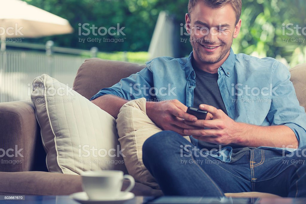 Young man texting on a mobile phone. stock photo