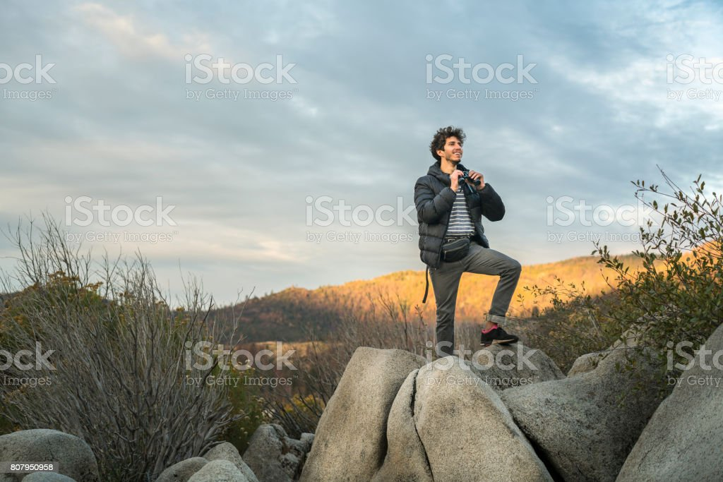 Young man, the traveling hipster, observing the Yosemite valley near by Old Flat Oak Road with the binocular at sunrise. stock photo