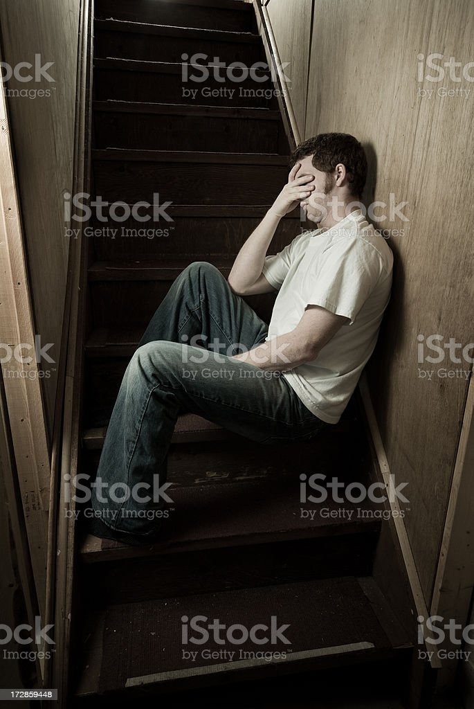young man thinking on stairs stock photo