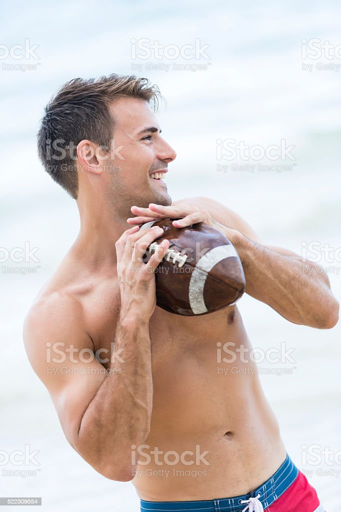 Young man throwing a rugby ball on the beach stock photo