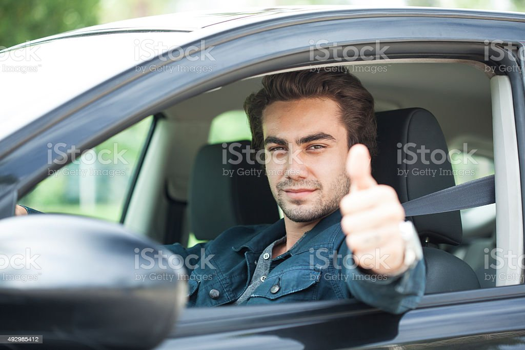 Young man thumbs up gesture in car stock photo