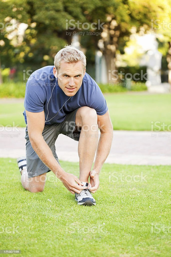 Young Man Ties His Shoe Laces stock photo