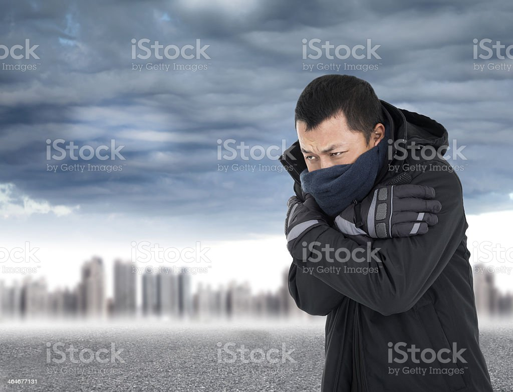 Young man tightening body in outdoors cold weather stock photo