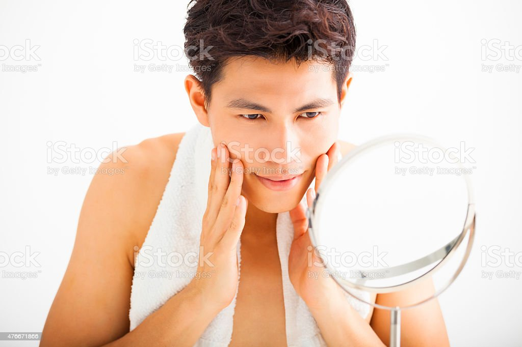 Young  man touching his smooth face after shaving stock photo