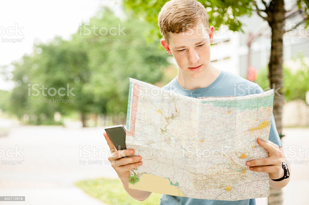 Young man tourist in urban, downtown city.  Map, cell phone. stock photo