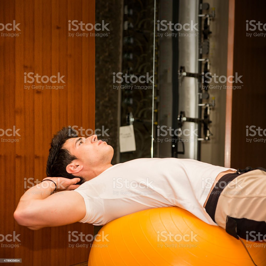 Young man training abs on fitness ball stock photo