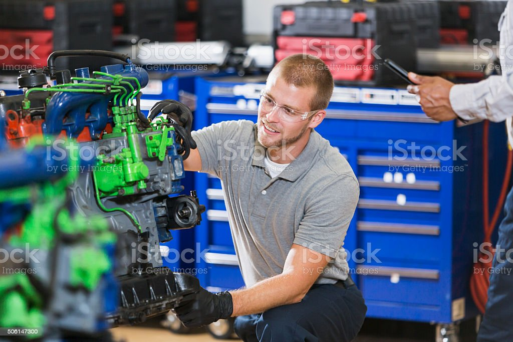 Young man training to be an auto mechanic stock photo
