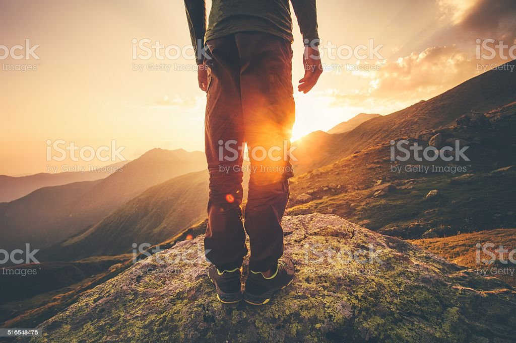 Young Man Traveler feet standing alone with sunset mountains stock photo