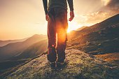 Young Man Traveler feet standing alone with sunset mountains