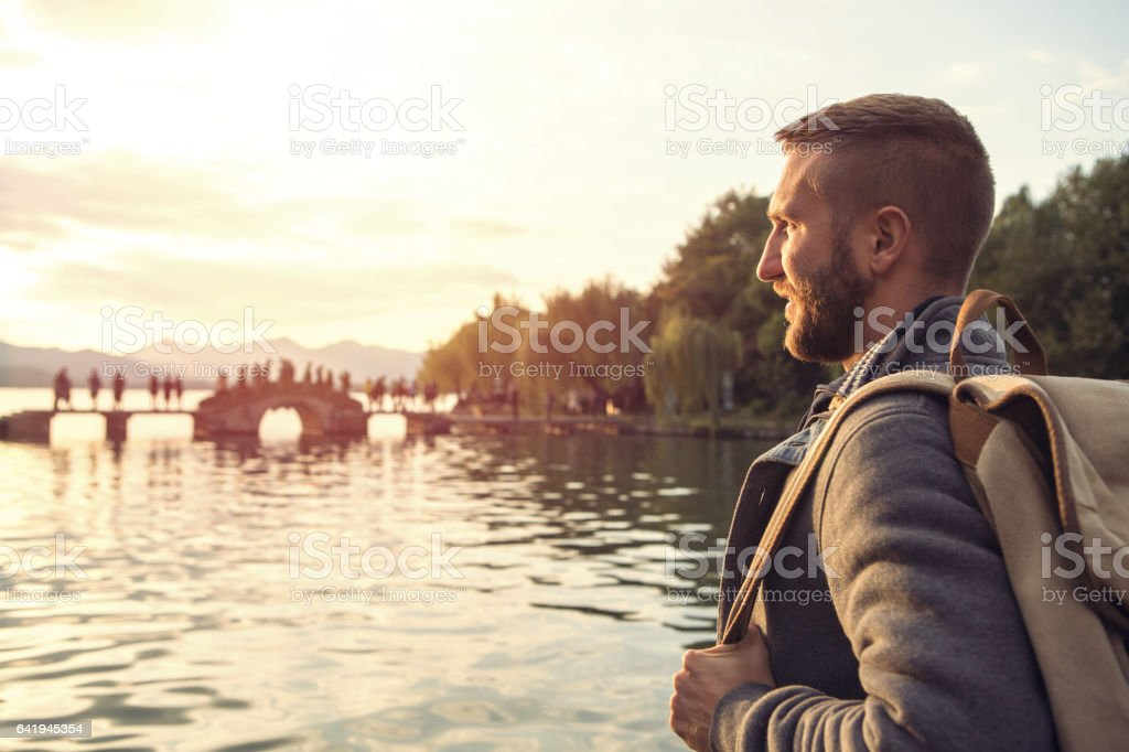 Young man traveling in China looks at landscape stock photo