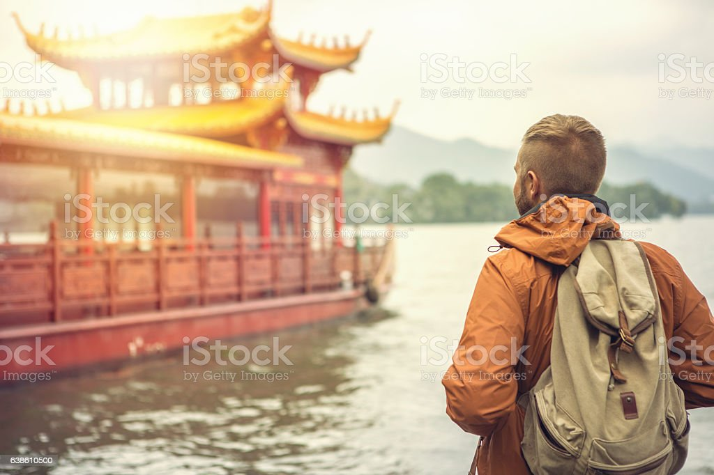 Young man traveling in China looks at pagoda on lake stock photo