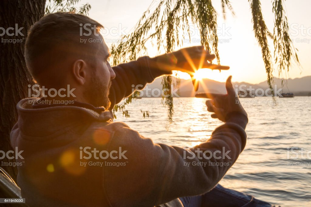 Young man traveling in China makes natural finger frame stock photo