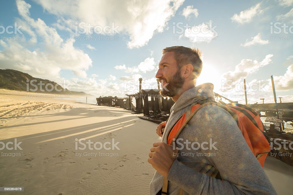 Young man traveling stands near Fraser Island Shipwreck stock photo