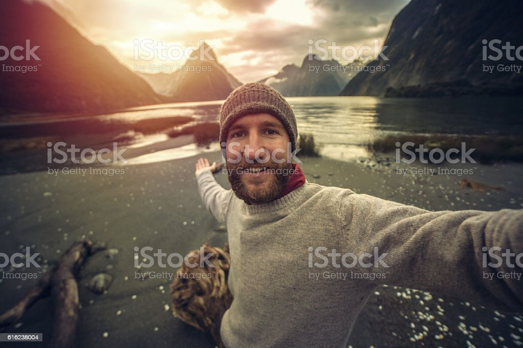 Young man traveling takes selfie portrait at Milford Sound, NZ stock photo