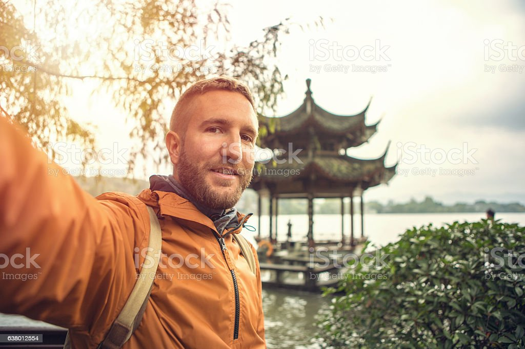 Young man traveling takes selfie portrait by the lake, China stock photo
