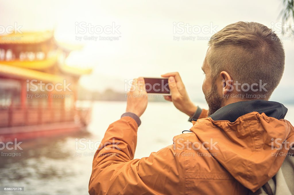 Young man traveling takes smart phone picture of pagoda stock photo