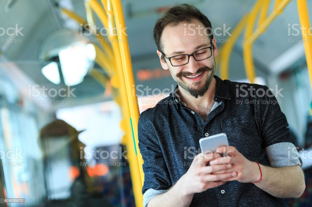 Young man traveling with bus and using smart phone stock photo