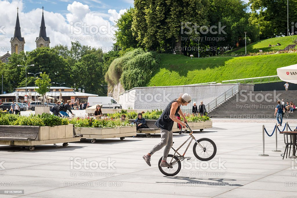 Young man tricking on BMX at square in Tallinn, Estonia