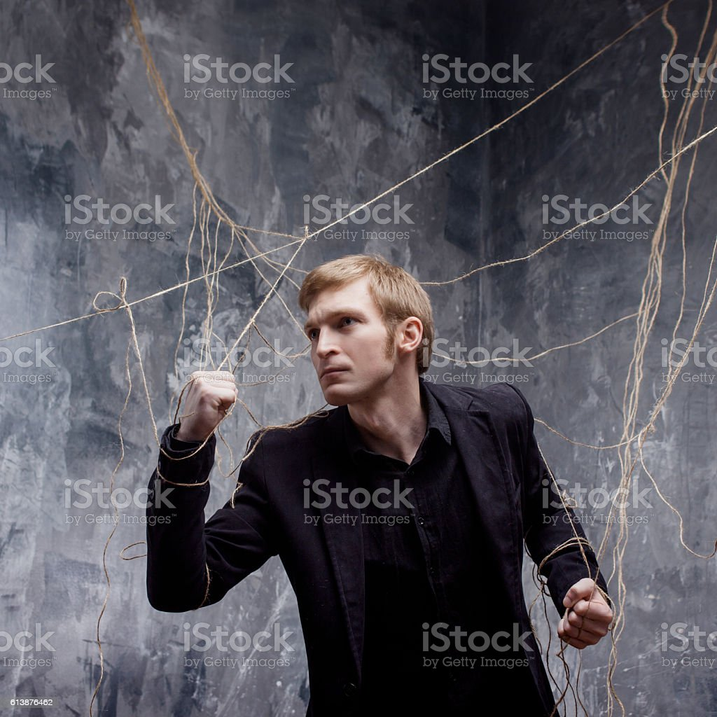 Young man tries to break the shackles. Concept of manipulation stock photo