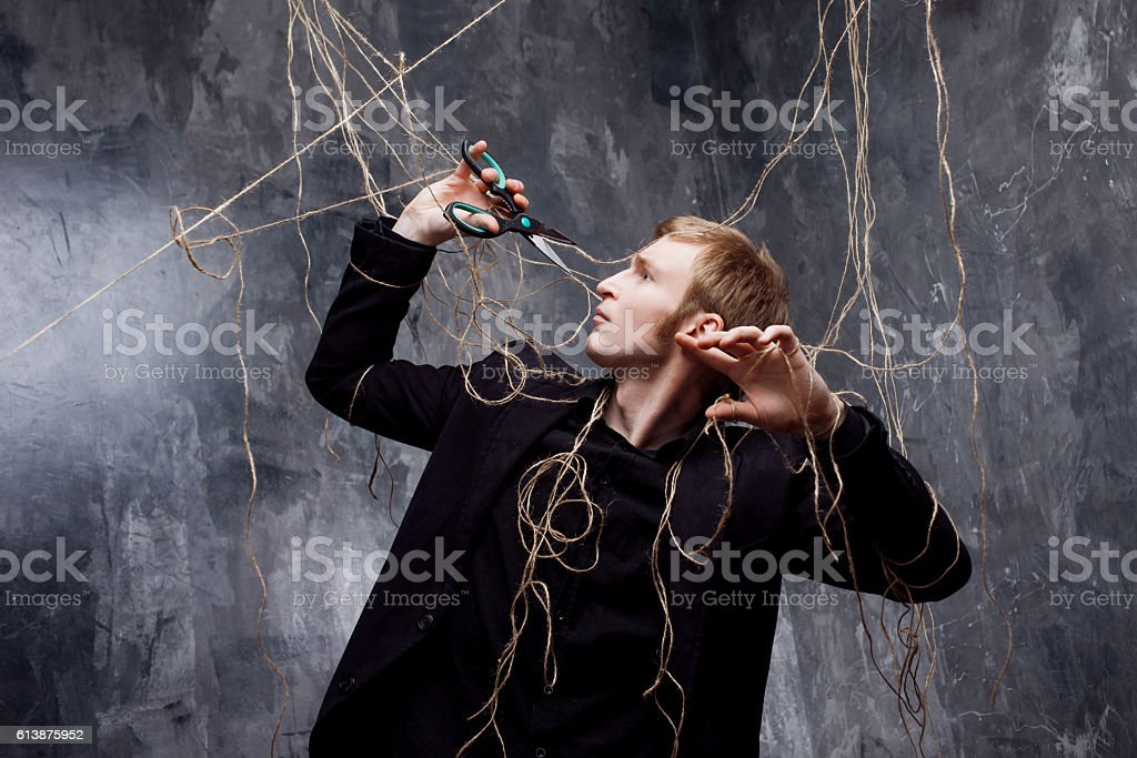 Young man tries to cut the straps with scissors. The stock photo