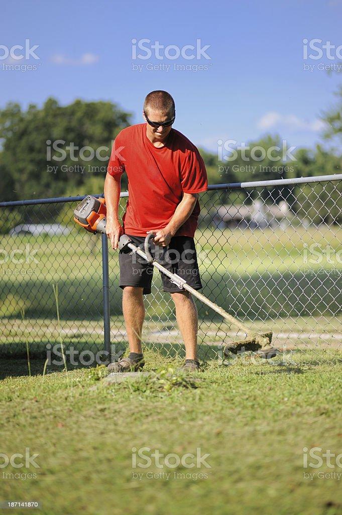 Young man triming yard royalty-free stock photo