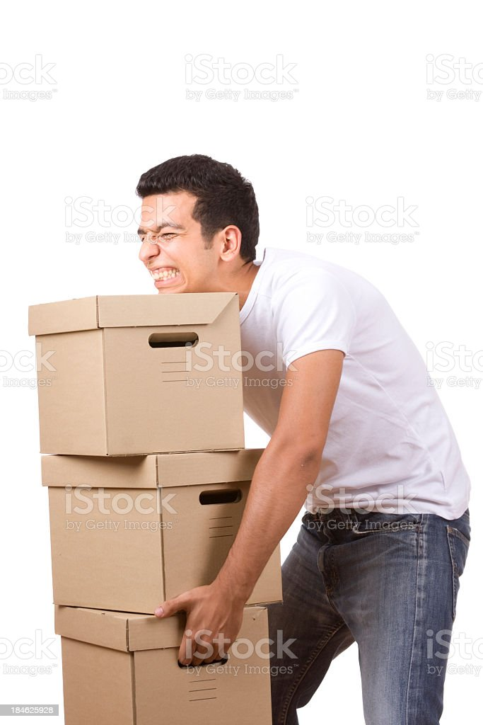 Young man trying to lift stacked heavy boxes stock photo