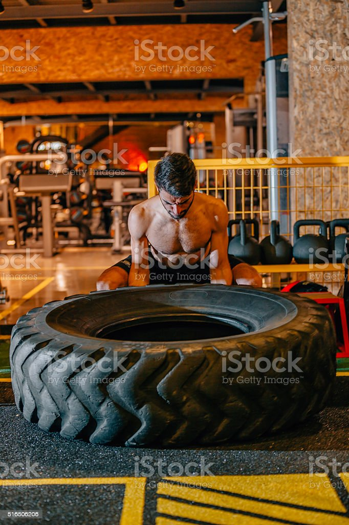 Young man turning tires at gym stock photo