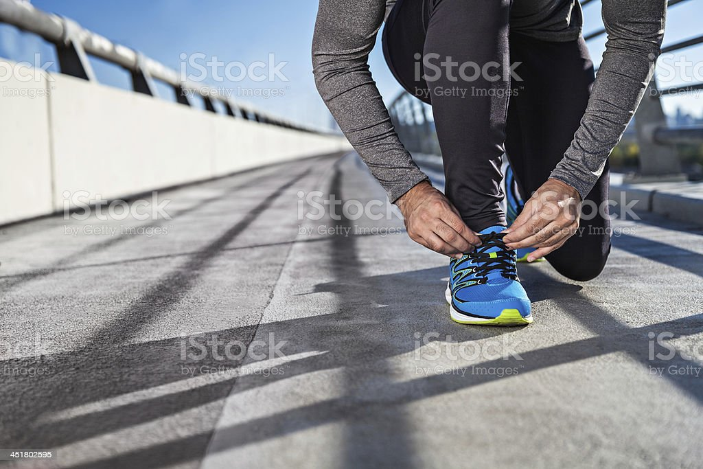 Young man tying his laces stock photo