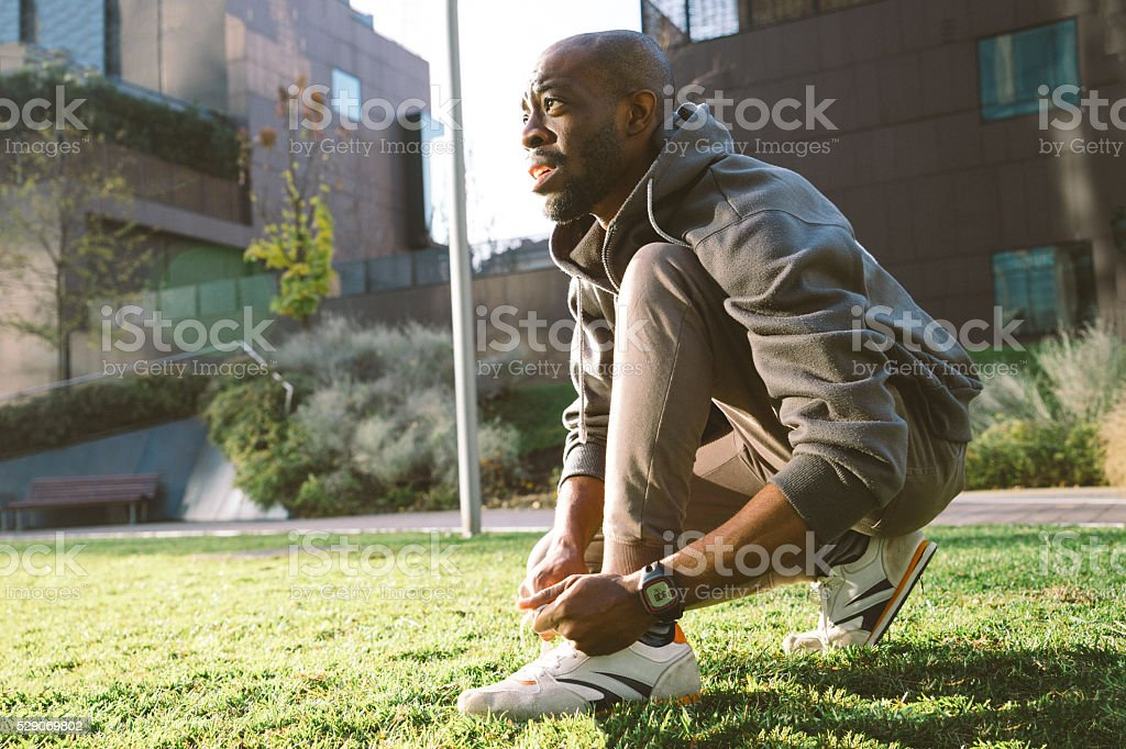 Young Man Tying His Shoelaces wearing sport clothes and smartwatch stock photo