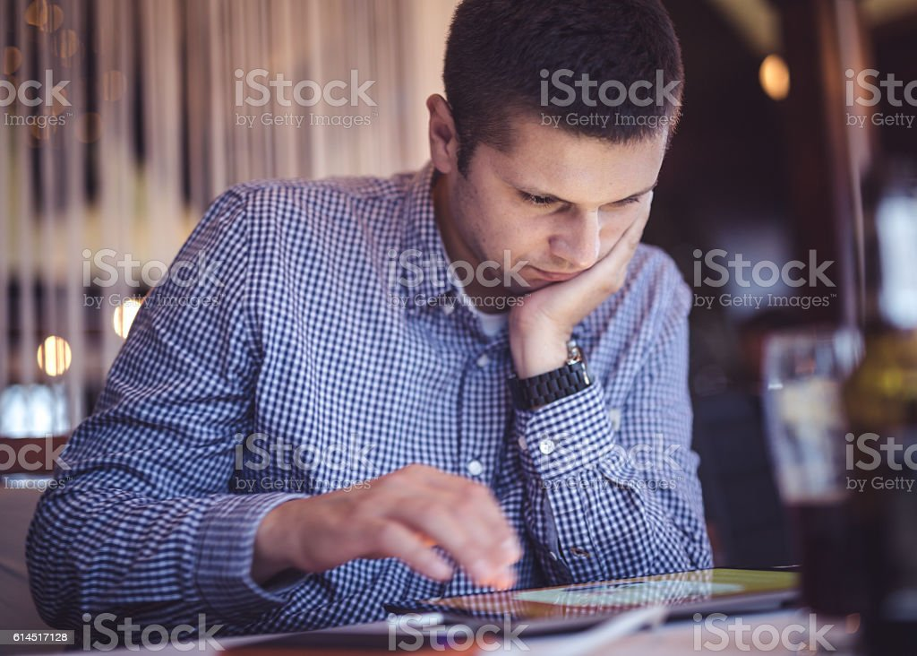 Young man typing on digital tablet stock photo