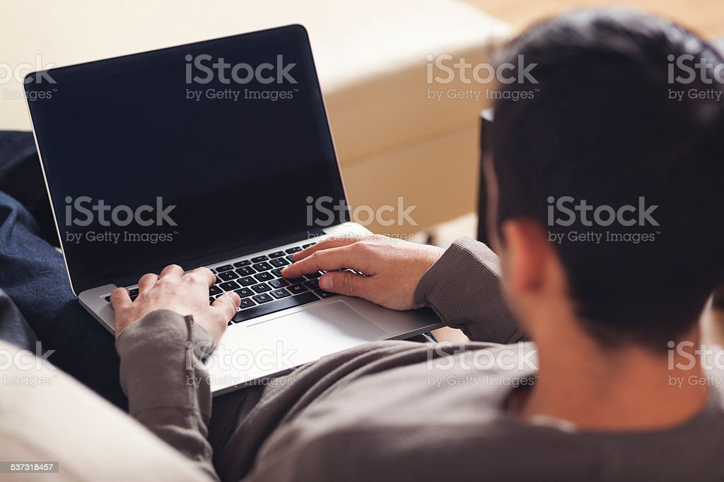 Young man typing on laptop stock photo