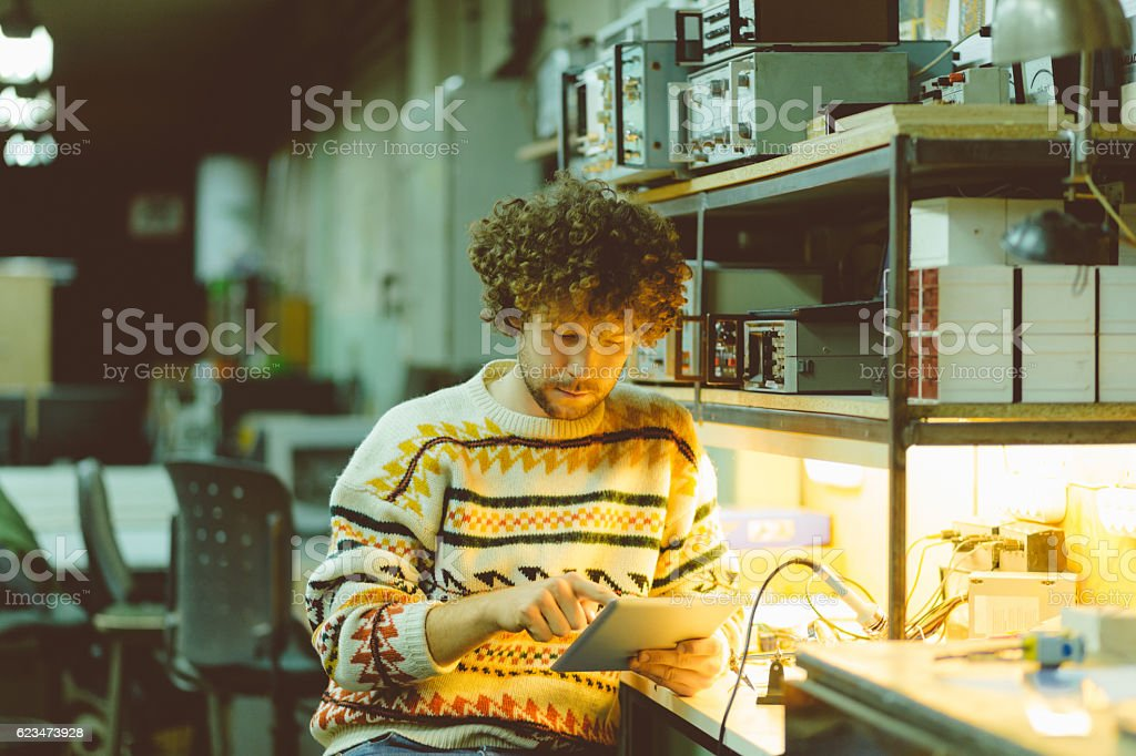 Young man using a digital tablet in an electronics workshop stock photo