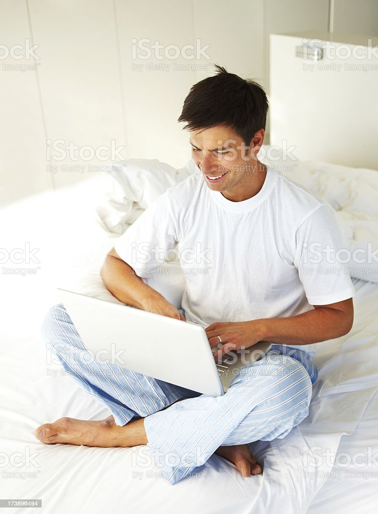 Young man using a laptop and smiling royalty-free stock photo