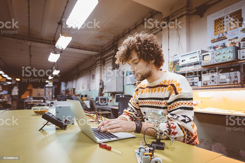 Young man using a laptop in an electronics workshop stock photo