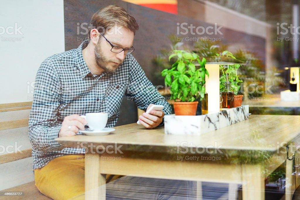 Young man using a smart phone in the restaurant royalty-free stock photo