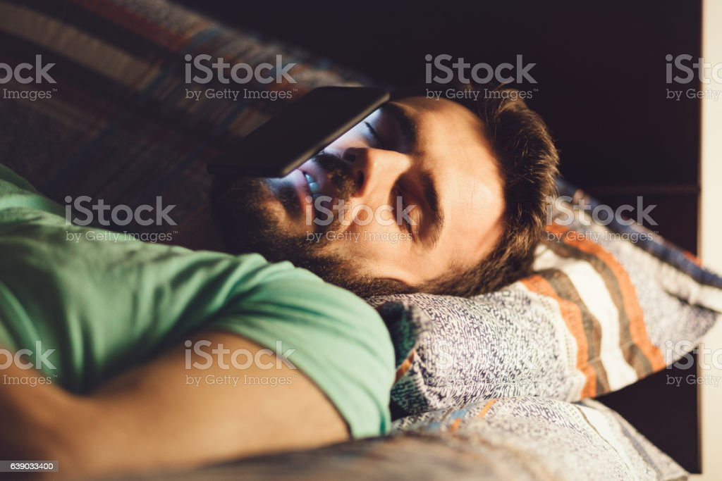 Young man using a smartphone in his bed stock photo